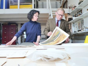 Vera Kaldewey und Magnus Gerdsen begutachten eine Sammlung Handzeichnungen
